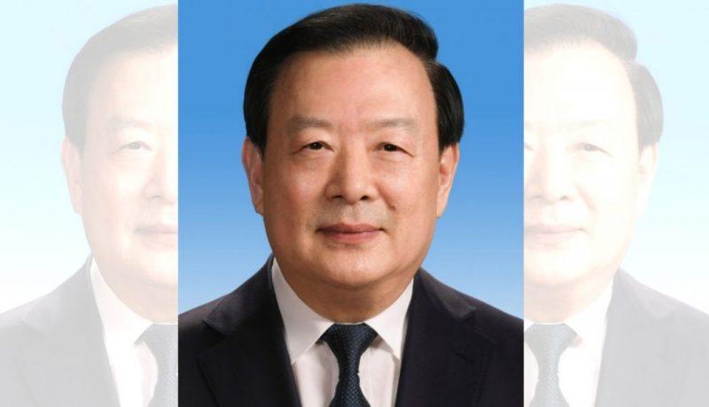 L'image est une photographie en plan serré sur le visage d'un homme de type asiatique, Xia Baolong, sur un fond bleu. Homme politique chinois, il est dirige le bureau des affaires de Hong Kong et Macao. Légèrement souriant, il est vêtu d'un costume. L'image est une combinaison de 3 images qui se superposent.