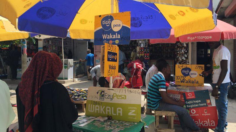 Photo du marché où des points de transfert d'argent sont installés sous des parasols colorés