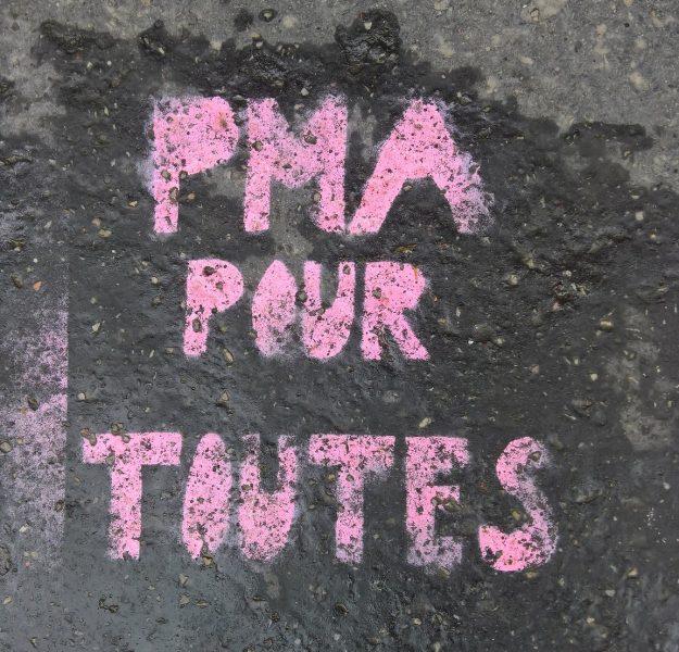 """Graffiti rose dont le message """" PMA pour toutes """" a été réalisé au pochoir sur un mur gris."""
