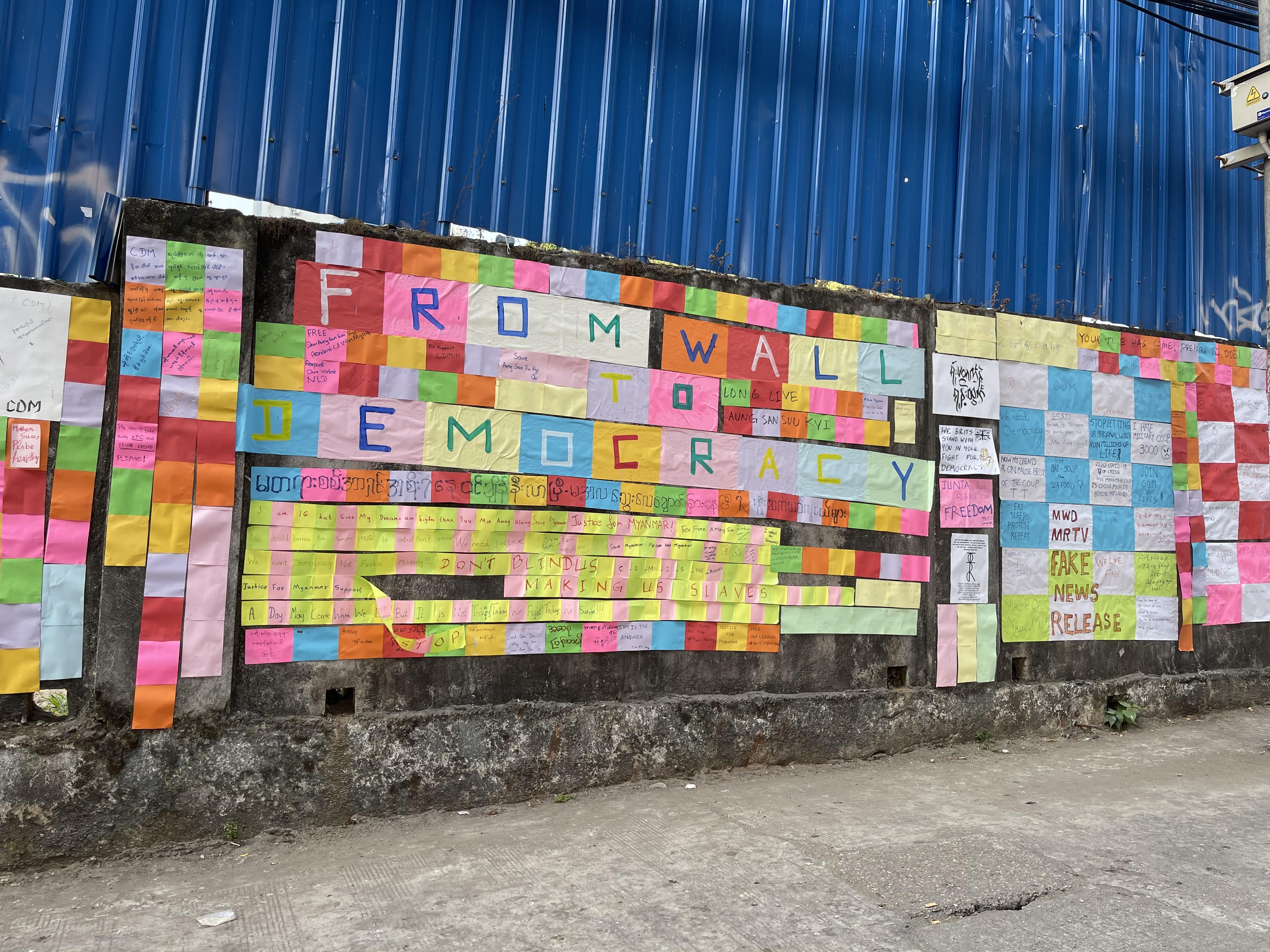 L'image montre un mur dit « mur de liberté » sur lequel une multitude de messages sont apposés, papiers de toutes les couleurs. On peut y lire en caractères plus gros : « From wall to Democracy » (Du mur à la démocratie). Les messages sont en anglais et en birman.