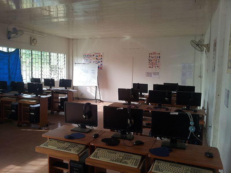 """L'image représente une salle avec de nombreux bureaux et ordinateurs. Personne n'est présent à l'image et aucune chaise n'est visible. On distingue un """"présentoir tableau"""". Les murs de la salle sont blancs. Deux ventilateurs sont fixés au mur, ainsi que quelques affiches. Une fenêtre apparaît sur tout le côté gauche de la salle et, sur une petite partie, un rideau bleu est suspendu."""