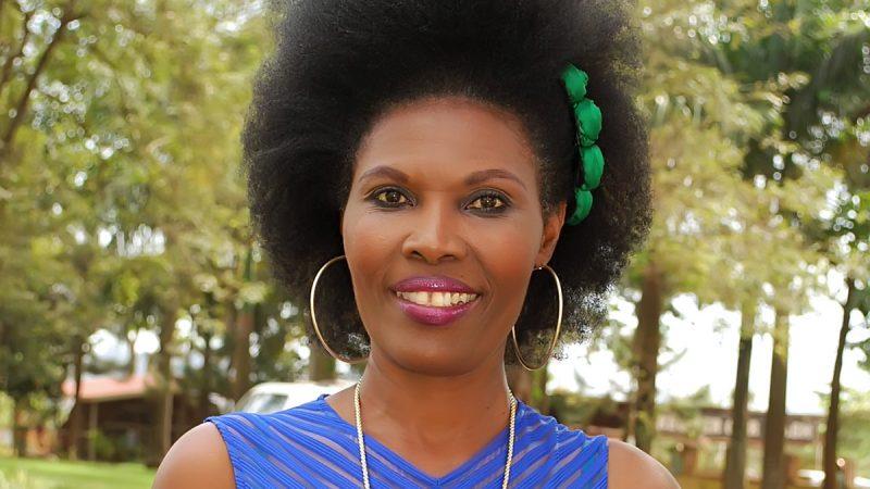 Усміхнена Шанталь Мутамуріза, позує на фоні дерев. Має афро-зачіску та носить великі сережки.