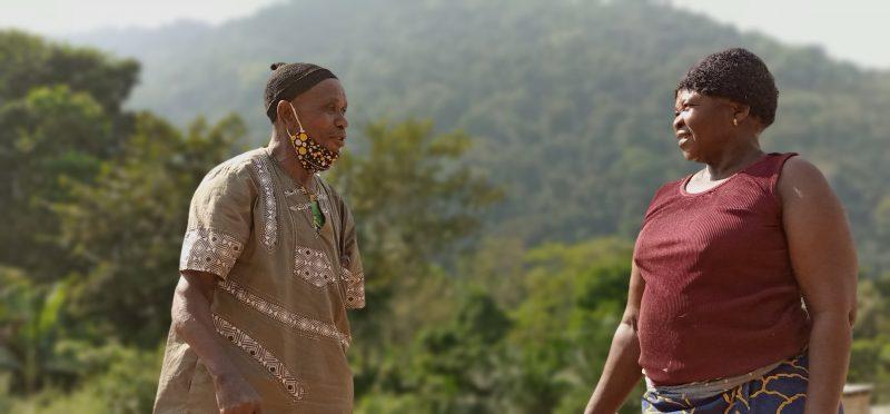 Лідер Нгіле, літній чоловік, із тканевою маскою на підборідді розмовляє із жінкою міцної статури.