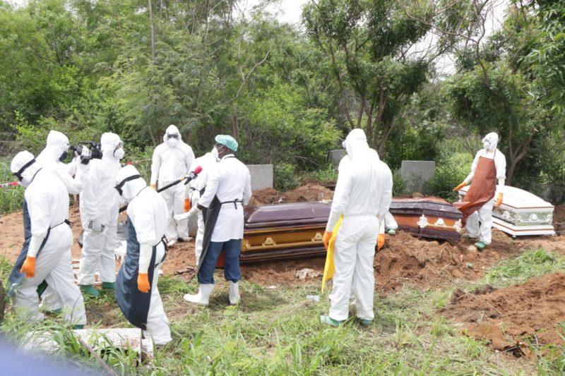 Des journalistes et des fossoyeurs, tous en combinaisons et avec des masques, autour de cercueils prêts à être enterrés
