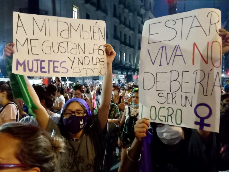 Milieu d'une manifestation. Deux femmes brandissent leurs pancartes à la caméra.
