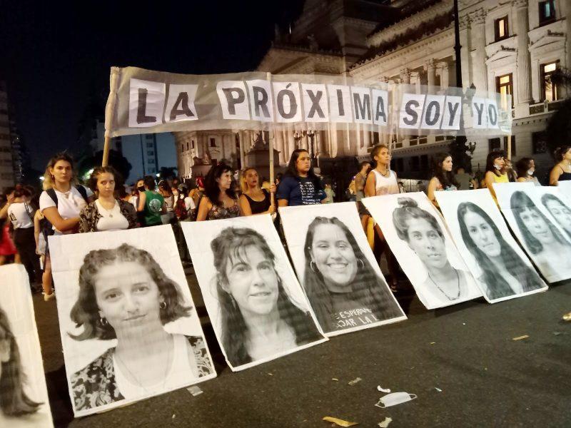 Première ligne de la manifestation. Des femmes portent une banderole et se tiennent derrière de grands portraits de femmes en noir et blanc.