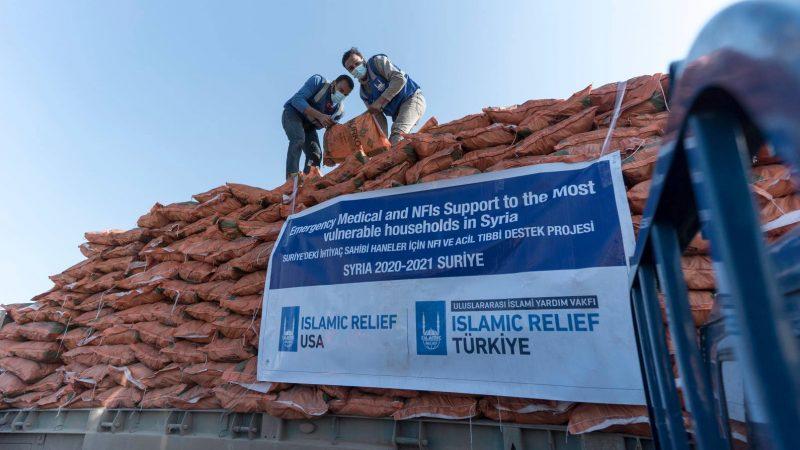 """Un monticule de sacs d'aide humanitaire en train d'être déchargé par deux hommes depuis un camion portant le logo """"Islamic Relief""""."""