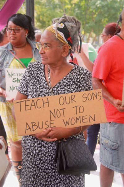 Cadrage sur une vielle femme, présente à la même manifestation que celle de la photo précédente, regarde au loin avec un air déterminé et porte la pancarte citée dans la légende.