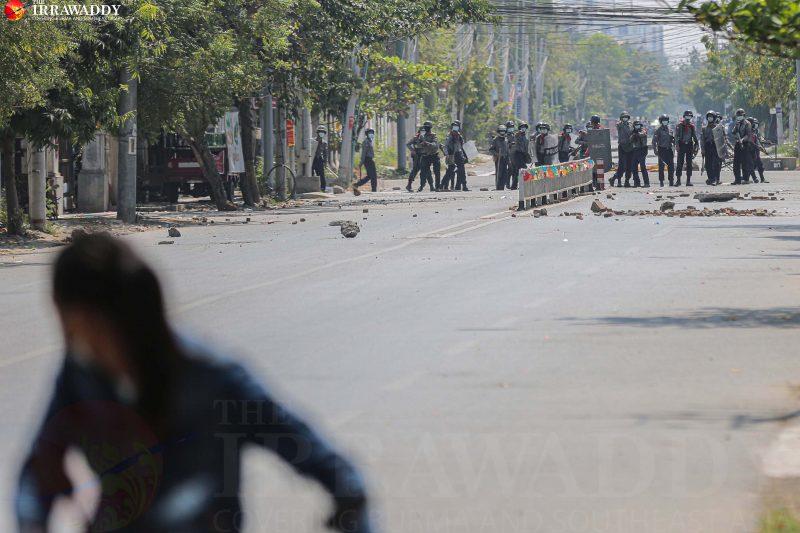 L'image est un plan dans une rue ou on distingue en arrière plan des policiers anti-emeute. Certains mettent en joue les manifestants (non visibles sur le plan). On voit sur la rue des pierres, des gravats. Au niveau des policiers, on distingue a priori une petite glissière de sécurité, ornées de rubans ou papiers de toutes les couleurs. En tout premier plan, on distingue une personne qui court pour s'éloigner des policiers. Cette personne est floue car elle est en mouvement. Le logo « The Irrawaddy » est visible en haut sur la gauche de l'image.