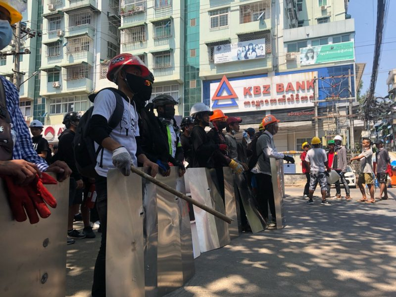 L'image, en légère contre plongée, montre des manifestants alignés. Ils portent des casques et des masques de protection faciale, et se protègent avec des boucliers. Certains sont armés de bâtons. Ils se trouvent dans la rue. Un immeuble d'habitations est visible en arrière plan. Une banque se trouve à l'angle de cet immeuble.