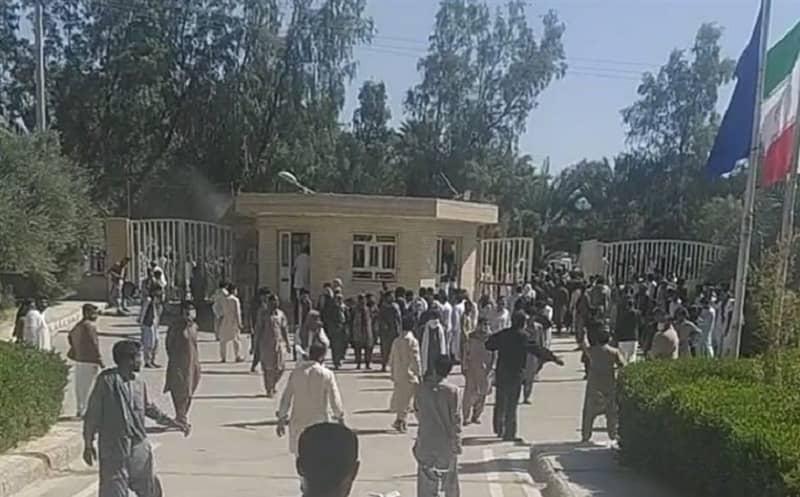 Un groupe épars de manifestants s'avance vers un grand portail. Au premier plan le drapeau de l'Iran et un drapeau bleu.