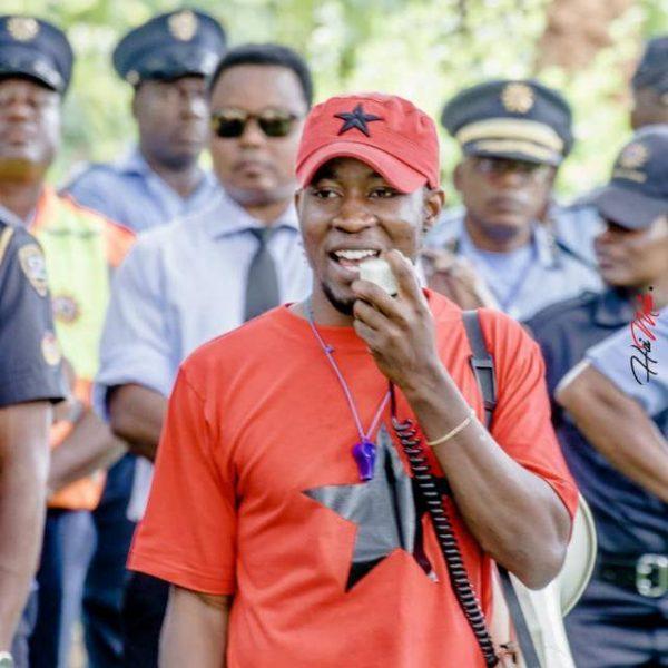 Cadrage en gros plan sur Job Amupanda pendant la manifestation et parlant dans un amplificateur de voix portable
