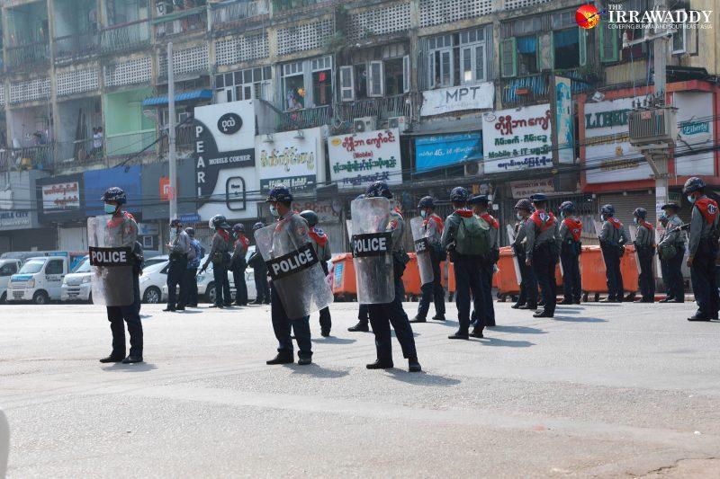 L'image montre plusieurs policiers anti-émeute, alignés dans une rue. Ils sont à l'arrêt. Ils portent un casque et un bouclier de protection avec l'inscription « police » dessus. En arrière plan, on distingue des magasins et des appartements juste au-dessus. En haut sur la droite, le logo du site « The Irrawaddy » est visible.