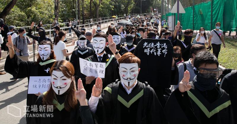 """Des étudiants et étudiantes portant pour la majorité d'entre eux des masque Anonymous. Certains brandissent des pancartes, d'autres font le """"salut à trois doigts""""."""