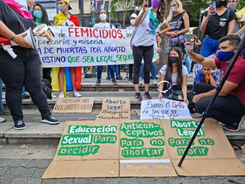 Un groupe de manifestants est réuni autour de pancartes posées sur le sol. En arrière-plan des manifestants portent une autre pancarte.