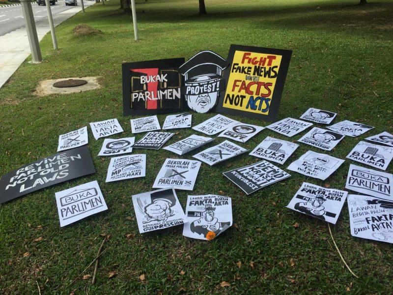 Des pancartes et affiches sont disposées sur une pelouse. Leurs slogans protestent contre l'ordonnance criminalisant les fake news.