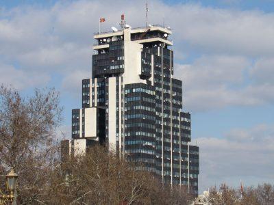 Un très grand bâtiment moderne est au centre de la photo. Le ciel est bleu, avec quelques nuages.