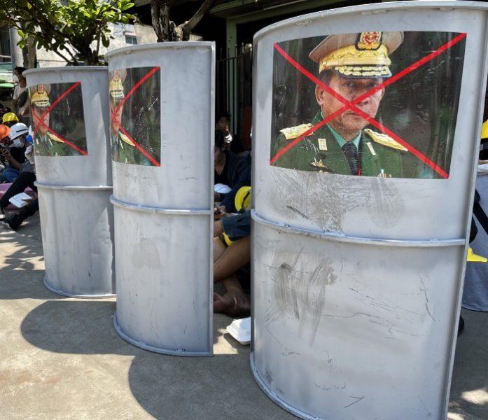 L'image montre 3 boucliers, posés au sol, dans la rue. La photographie du général, auteur du coup d'Etat, a été collée sur le bouclier, une croix de couleur rouge lui barrant le visage. On distingue plusieurs personnes derrière ces boucliers.