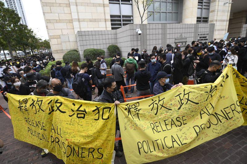 """L'image montre une foule de personnes, portant un masque de protection faciale, dans la rue, regroupée devant et autour du tribunal. En 1er plan, plusieurs personnes tiennent de grandes banderoles avec l'inscription, en chinois et en anglais : """"Release all political prisoners"""" (Libérez tous les prisonniers politiques)."""