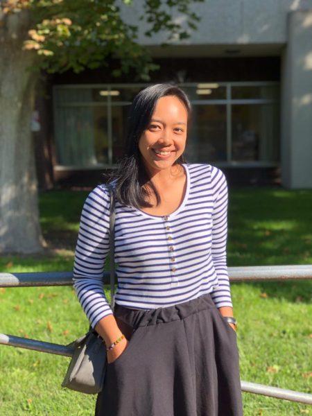 Photo en pied de Ni Nyoman Clara Listya Dewi, souriante et décontractée dans un jardin.