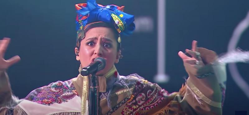 Un gros plan sur la représentante de la Russie à l'Eurovision en train de chanter. Elle porte des habits traditionnels et on la sent très imprégnée de ses propos.