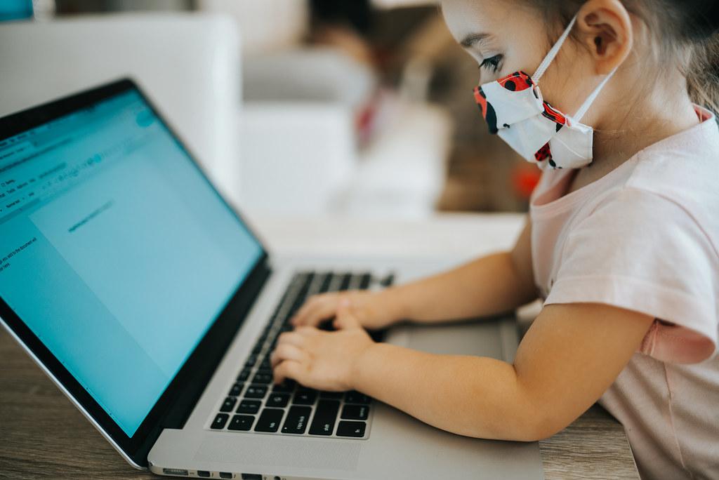 Une fillette portant un masque en tissu est concentrée sur le clavier d'un ordinateur portable.