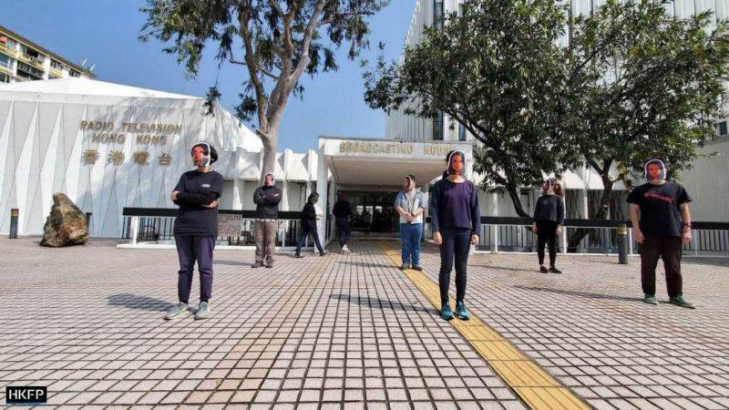 Des personnes masquées se tiennent debout à 1 mètre 50 de distance sur une place, on aperçoit des inscriptions sur le bâtiment derrière eux indiquant qu'il appartient à la radiotélévision hongkongaise.