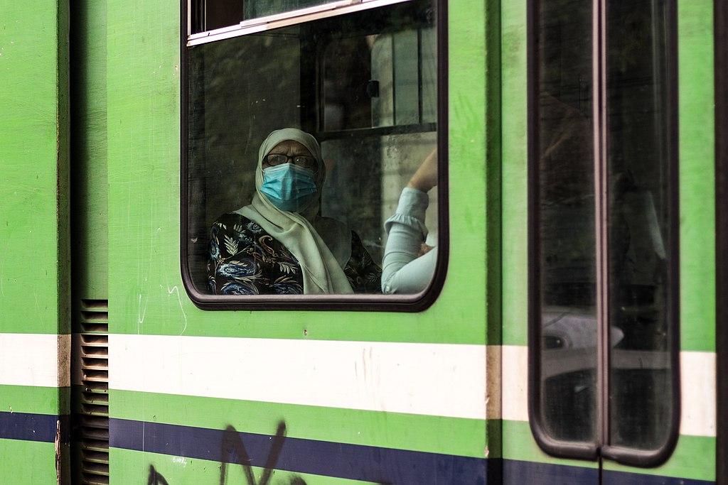 Une femme portant le hijab et un masque de protection faciale regarde par la fenêtre d'une rame de métro.