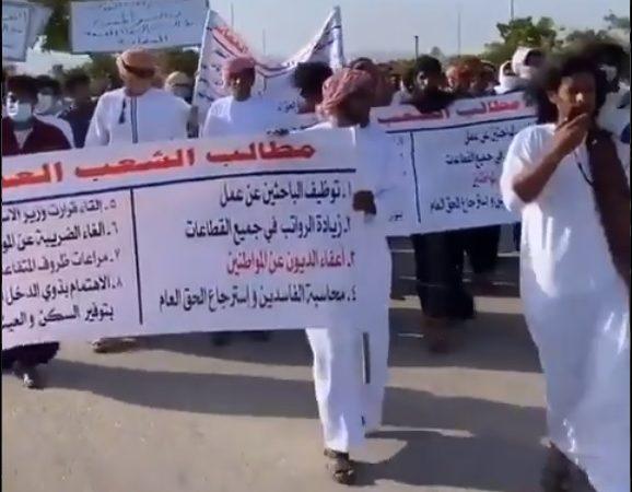 Un groupe de jeunes hommes omanais défilent tenant une pancarte à plusieurs.