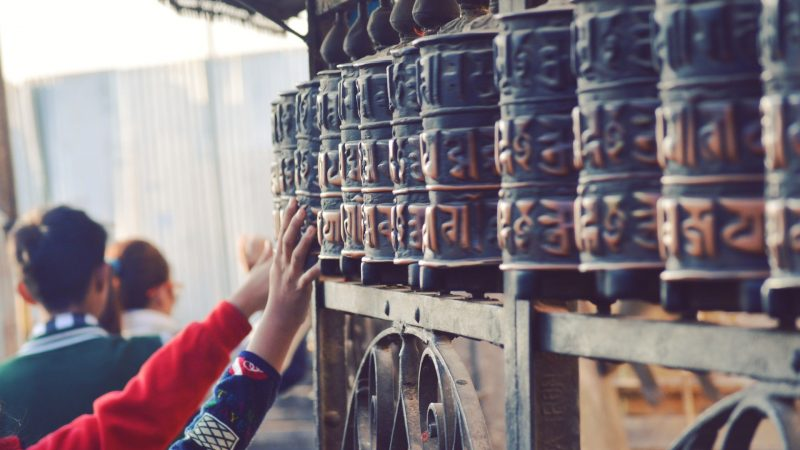 Pilgrims touching Prayer wheels in an ancient temple in Gokarneshwor, Nepal. Photo by Bishal Sapkota. Used under a Pexels License.