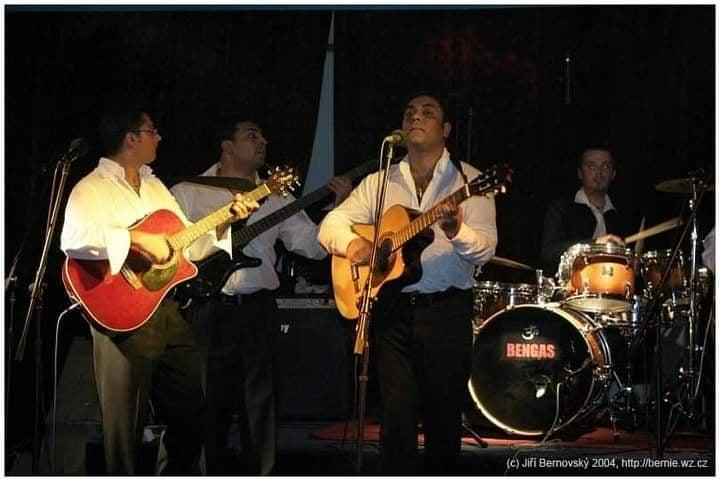 Le groupe Bengas en concert. Trois guitaristes et un batteur sont éclairés par des projecteurs, ils échangent des regards entre eux.