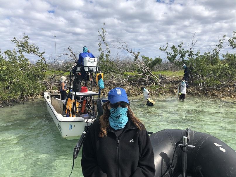 Le premier plan montre une jeune femme de face en zodiac sur des eaux limpides. Derrière elle, une équipe nettoie le rivage.