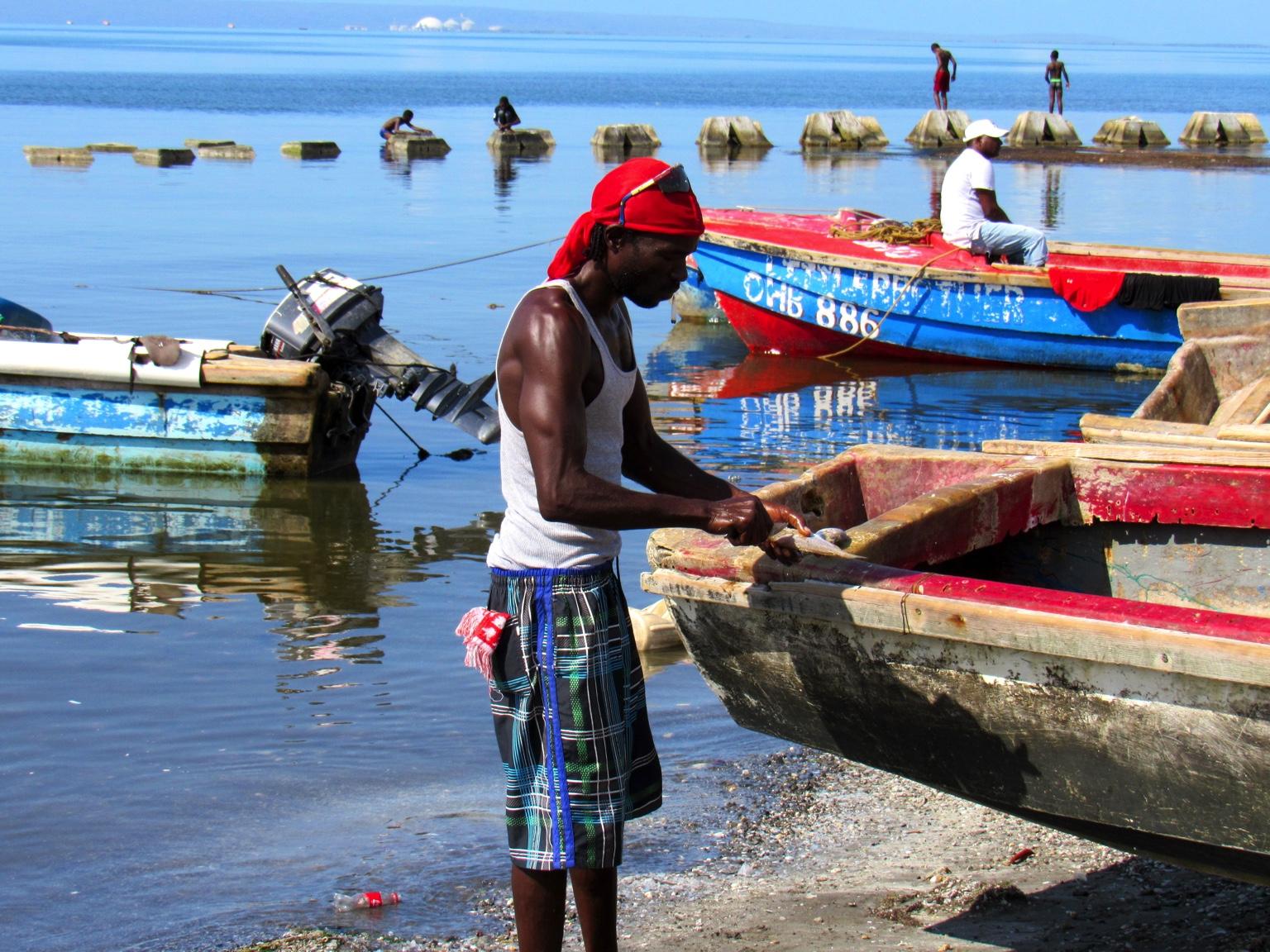 En premier plan, un pêcheur caribéen découpe un poisson sur le bord de son bâteau de pêche en bois. Une bouteille en plastique de Coca-Cola flotte derrière lui. En arrière-plan, d'autres pêcheurs dont un est assis sur sa barque colorée.