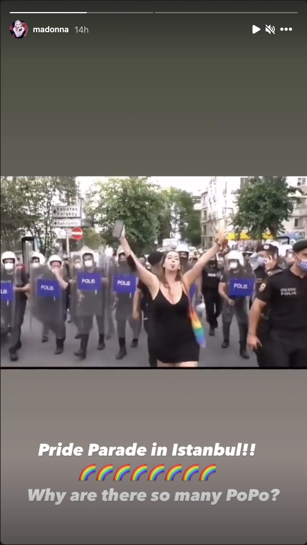 Une femme lève les bras et marche devant de nombreux policiers alignés