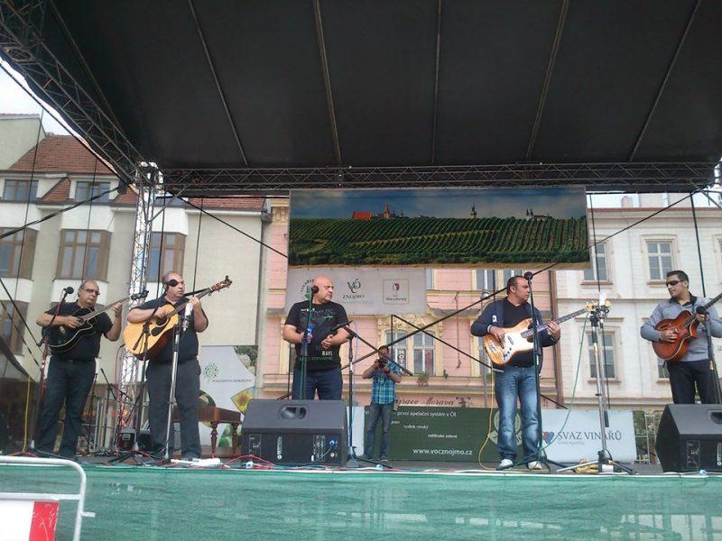 Un groupe de cinq musiciens cinquantenaires sur une scène, dont quatre tiennent une guitare/
