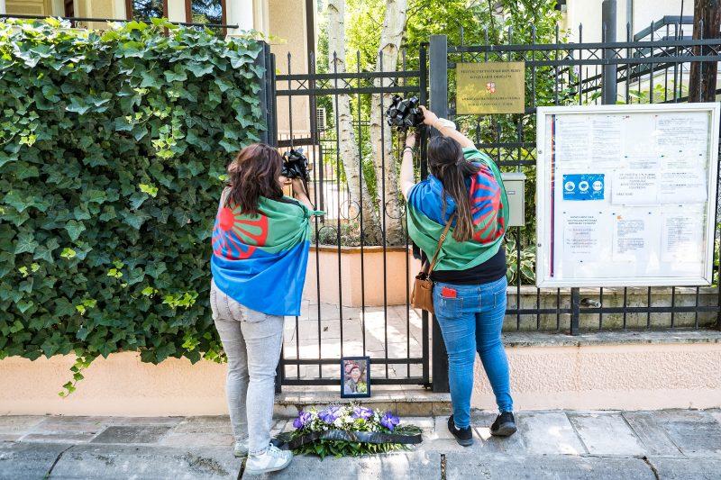 Deux manifestantes posent des rubans noirs sur le grillage de la porte d'entrée de l'ambassade. Elles portent un drapeau rom sur les épaules. À leurs pieds se trouvent des fleurs et une photo de Stanislav Tomaš.