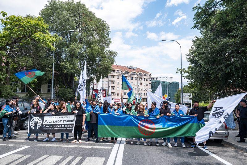 Des manifestants sont dans la rue et brandissent des pancartes, ainsi que des drapeaux roms et une pancarte représentant le poing du mouvement Black Lives Matter.