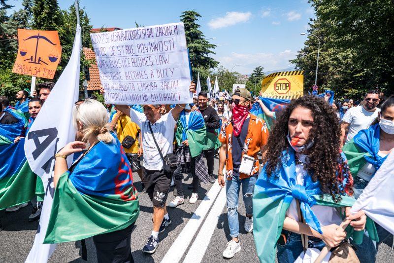 Des manifestants marchent dans la rue. Ils portent sur les épaules des drapeaux roms et brandissent des pancartes.