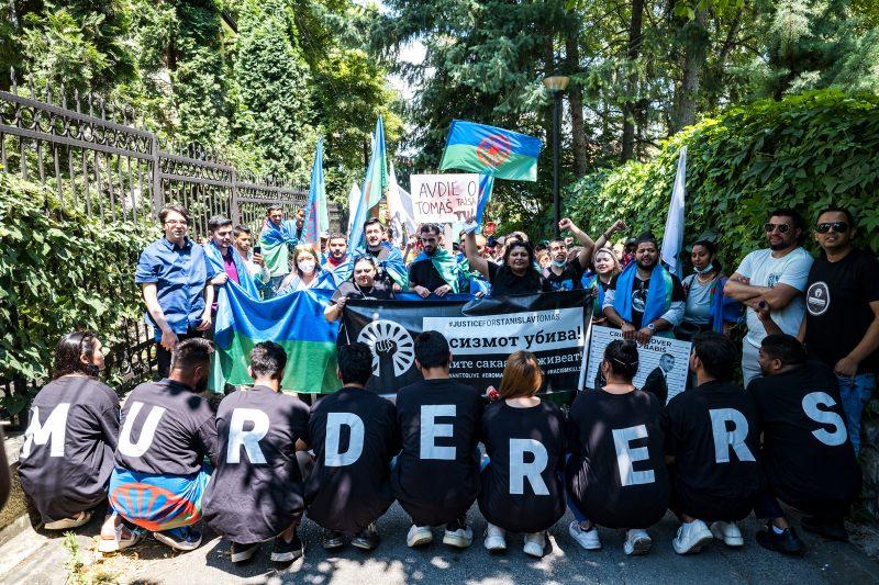Au premier plan, neuf manifestants sont agenouillés de dos. Ils portent des T-shirts noirs sur chacun desquels est inscrite une lettre. Mises bout à bout, elles forment le mot « assassins ». Au second plan se trouve un groupe de manifestants qui brandissent des pancartes et des drapeaux roms.