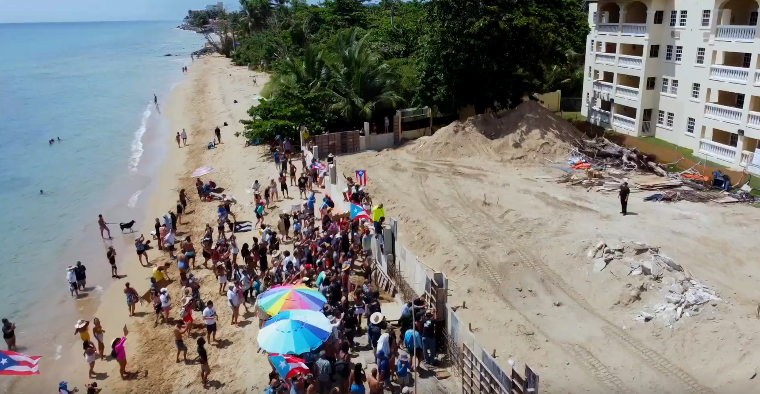 Protesters in the municipality of Rincón on the western coast of Puerto Rico have established a permanent presence at the construction site of a swimming pool that is being rebuilt after hurricane Maria destroyed it in 2017. Opponents of the construction say it is being built illegally. Screenshot from YouTube video uploaded by Carlos Mercado.
