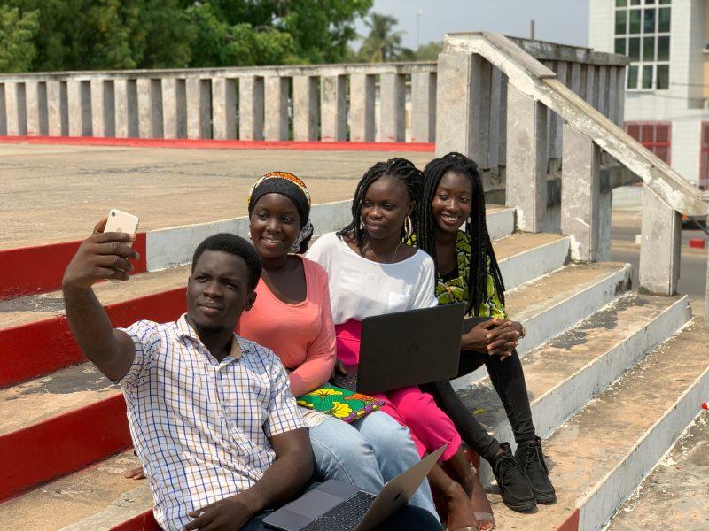 Quatre jeunes Nigérians se prennent en photo à l'aide d'un smartphone, sur un escalier en béton.