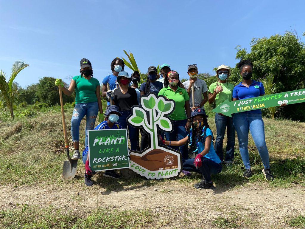 Photo de groupe de 12 jeunes caribéens portant leur masque sanitaire. Certains tiennent des pelles, d'autres des panneaux portant les messages «Je viens juste de planter un arbre», ou encore «Plante comme une rock star».