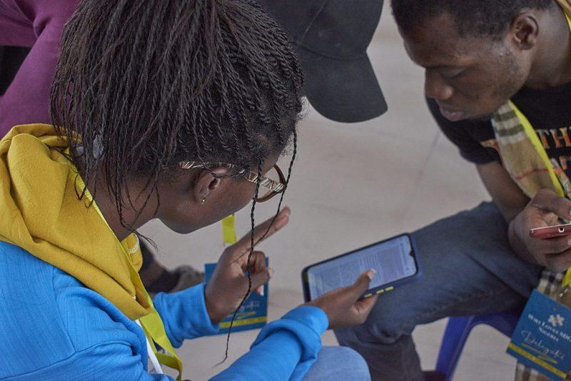 Une jeune femme montre son écran à deux hommes, qui se penchent pour mieux voir.