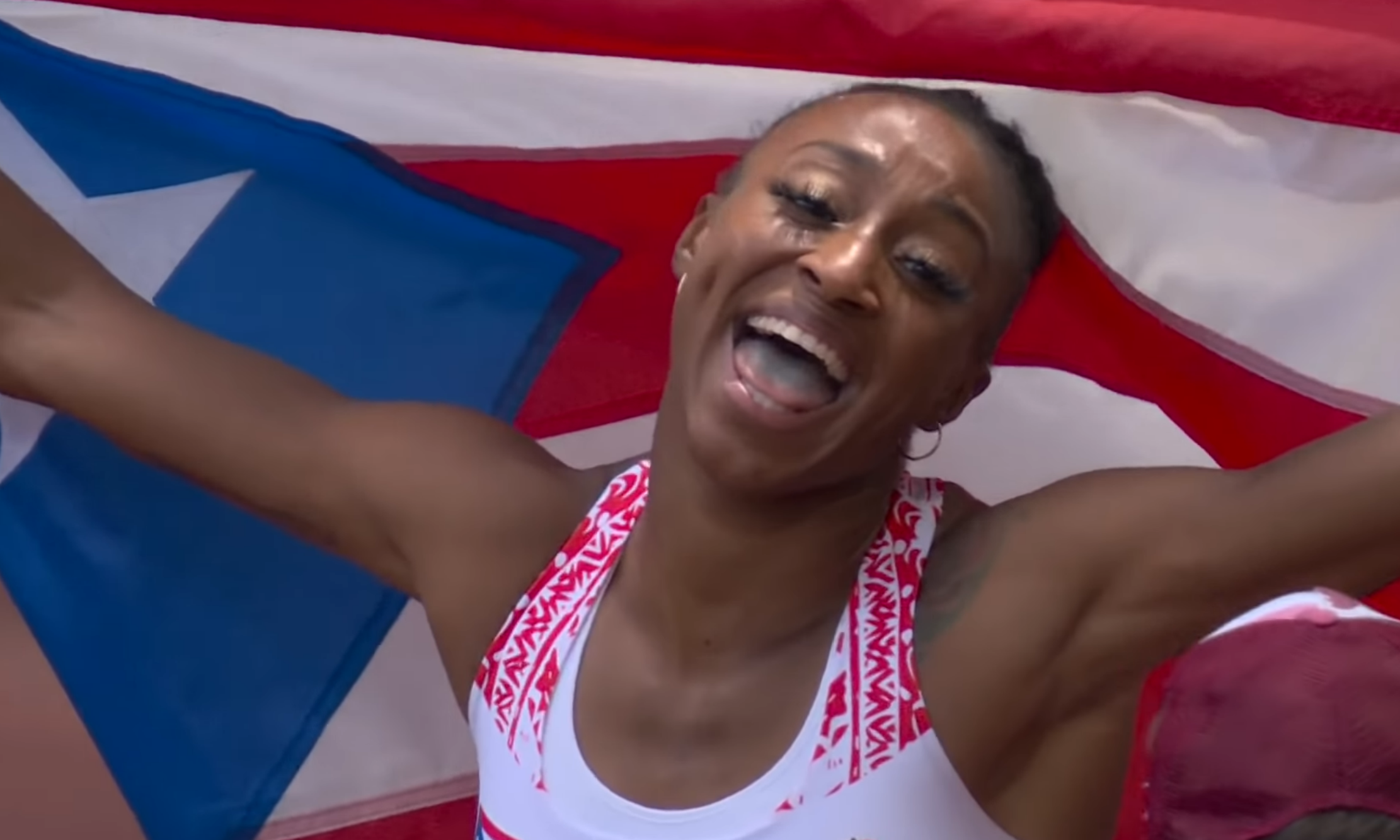 Jasmine Camacho-Quinn proudly displays the Puerto Rican flag after winning a gold medal in the Tokyo 2020 Olympics (held in 2021). Screenshot from video.