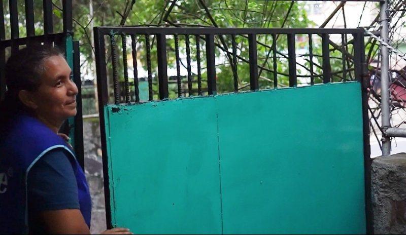 Une femme est en train d'ouvrir le portail du lycée.