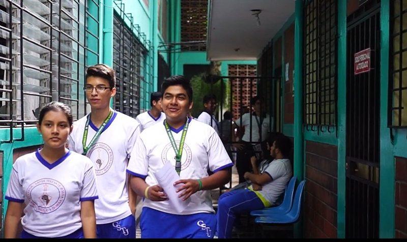 3 jeunes en uniforme, une fille et deux garçons, marchent dans l'enceinte de leur lycée.