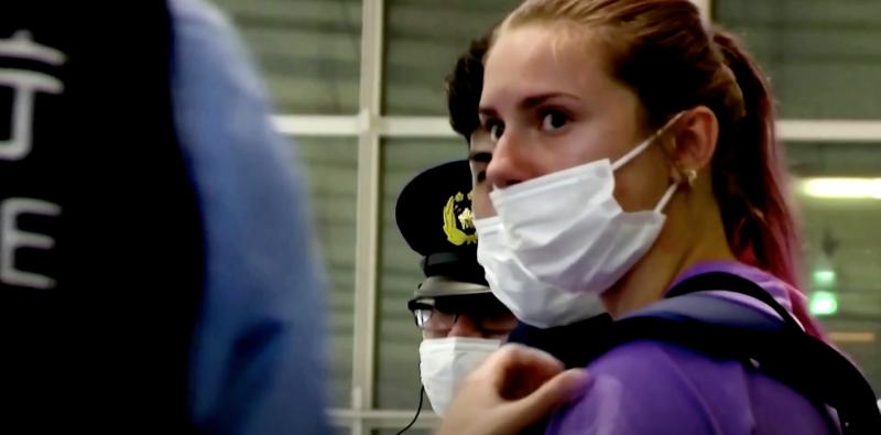 """La sprinteuse biélorusse Krystsina Tsimanouskaya s'adresse à la police à l'aéroport Haneda de Tokyo le 1er août 2021. Capture d'écran d'une <a href=""""https://www.reuters.com/lifestyle/sports/exclusive-olympics-belarusian-athlete-says-she-was-taken-airport-go-home-after-2021-08-01/"""">vidéo</a> en ligne de Reuters."""